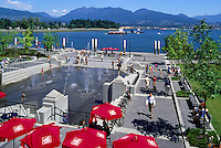 """Mill Marine Bistro - an Outdoor Restaurant Cafe with Red Sun Umbrellas, and Children playing at Water Park, along Waterfront at """"Coal Harbour"""", in the """"West End"""" of Vancouver, British Columbia, Canada, in Summer.  The North Shore Mountains (Coast Mountains) rise in the background."""