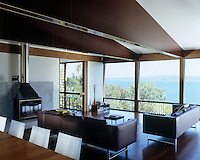 The row of picture windows in the simply furnished living/dining room offer uninterrupted and spectacular views of the Tasman Sea