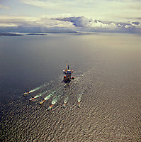 Oil production platform under tow from construction yards on the west coast of Scotland towards its site in the North Sea. Aerial..