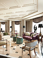 The sitting room of a luxurious, spacious apartment. Walls covered in marbleised hand painted paper and a polished floor creates an atmosphere where classic and modern elements coexist comfortably in a totally contemporary space.