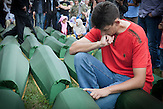 A Bosnian man is mourning at the coffin of a close relative killed during the 1995 Srebrenica genocide.