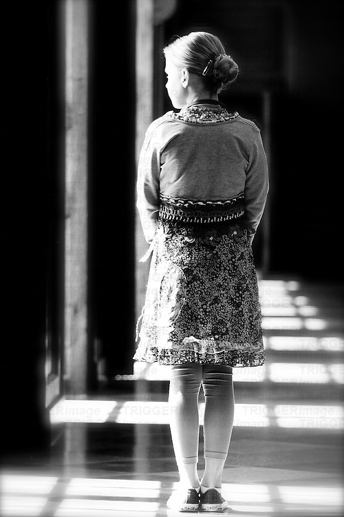 Young girl wearing a summer dress standing alone in a long corridor with sunlight shining through windows