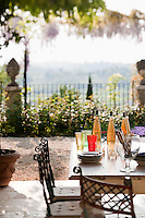 A table laid out for an informal lunch on the terrace benefits from the beautiful views of the surrounding hills and the nearby flowering wisteria
