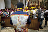 Switzerland. Canton Valais. St-Maurice. Africa Saints Pilgrimage (P&egrave;lerinage aux Saints d'Afrique). Religious <br /> ceremony in St-Maurice's abbey. African women and men gather for a catholic mass. A man wears a shirt with drawing of &quot;Our Lady of F&aacute;tima &quot; a title for the Virgin Mary due to her reputed apparitions to three shepherd children at F&aacute;tima, Portugal in 1917. The title of Our Lady of the Rosary is also sometimes used to refer to the same apparition. According to religious tradition, Mary was an Israelite Jewish woman and the mother of Jesus. Among her many other names and titles are the Virgin Mary or Blessed Virgin Mary, Mother of God, and Saint Mary in Western churches, Theotokos in Orthodox Christianity, and Maryam, mother of Isa in Islam. 2.06.13 &copy; 2013 Didier Ruef