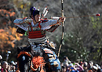 "Dressed in ornate period costume, a member of the Toyama-ryu ""yabusame"" horseback archery group shoots an arrow at a target during a yabusame ritual in Machida, western Tokyo, Japan on Nov. 28 2010. During the late Heian era (794 to 1185) and Kamakura era (1185-1333) such archery was the domain of high-ranked samurai and was used as a military training exercise to keep samurai prepared for war. .Photographer: Robert Gilhooly"
