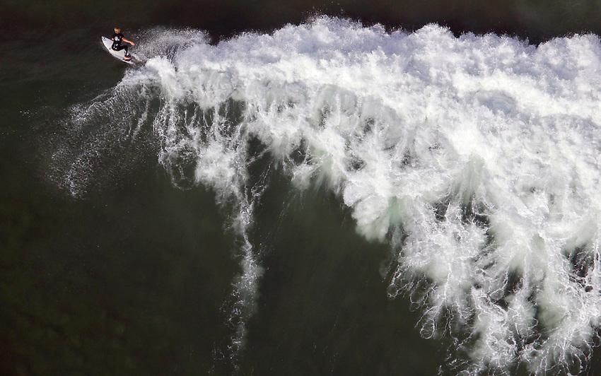 MANASQUAN, NJ - (Sept. 13, 2013) -Manasquan native Pat Schmidt, 19, rides a huge September swell at Manasquan Inlet.