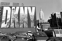 USA. New York. Huge signboard on the wall for designer women's clothing Donna Karan New York (DKNY). Statue of Liberty and view on manhattan. Empire State Building. Parking lot with cars. 20.01.98 © 1998 Didier Ruef
