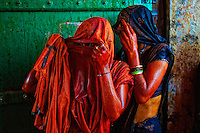 Two ladies looking through the veil. They used it to protect themselves from colored water which was being thrown at them.