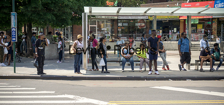 Commuters wait at a bus stop in the Bedford-Stuyvesant neighborhood of Brooklyn in New York on Saturday, July 2, 2016. (© Richard B. Levine)