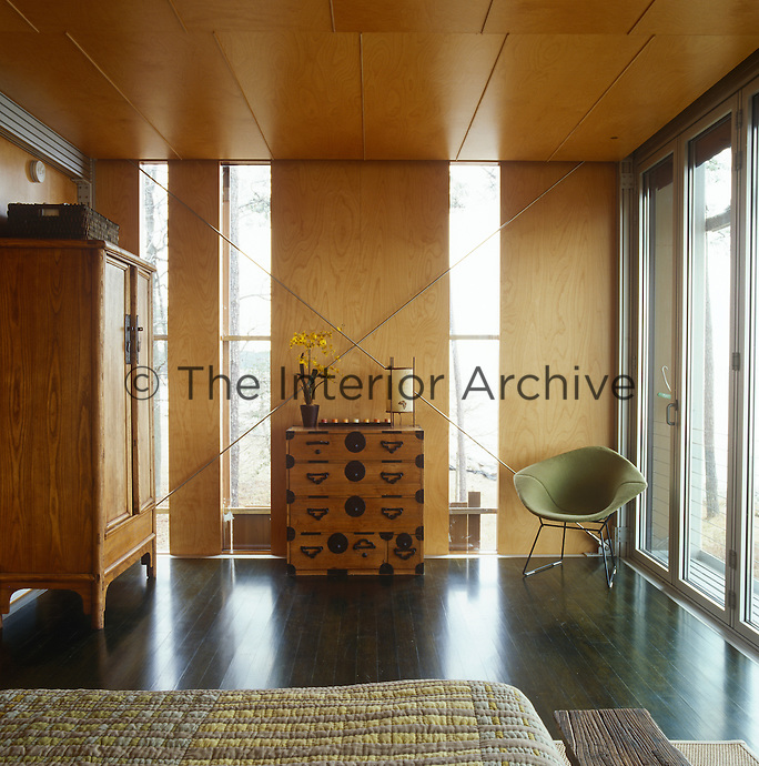 An antique Japanese chest of drawers and a Diamond chair by Harry Bertoia occupy one end of the bedroom