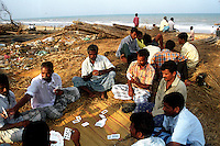 Men playing cards at Velankanni beach.Nagapattinam.India.