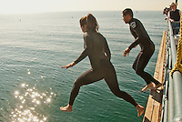 Reina Alvarez, 31, and Sandy Gallardo, 21, jump into the ocean from the Santa Monica Pier while participating in a Santa Monica Harbor Patrol rescue drill on Friday, December 9, 2011.
