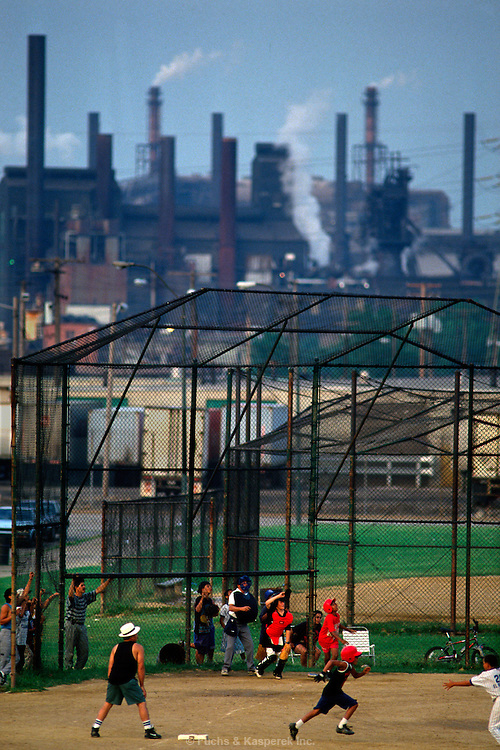 A steel mill provides the backdrop for a baseball game near downtown Cleveland, OH.