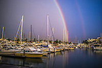 Fine Art Photograph of a double rainbow with water reflections in the ocean marina at Puerto Vallarta, Mexico.<br />