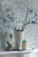Small chocolate and handmade fabric Easter eggs with colourful bird decorations adorn cherry blossom in a vase on the mantlepiece