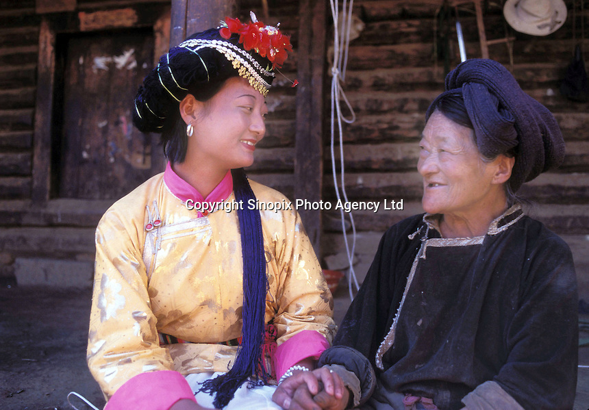 """Ai Li Zhi Ma, 19, and her 80-year-old grandmother, Ge Zhama, the head of her household of 13 people on Lugu Lake, Yunnan. Ge Zhama is the matriarch, the family elder and chief. Women from the Mosuo tribe do not marry, take as many lovers as they wish and have no word for """"father"""" or """"husband"""". But the arrival of tourism and the sex industry is changing their culture...PHOTO BY SINOPIX"""