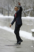 Chicago, IL - December 19, 2008 -- United States President-elect Barack Obama waves to kids in the windows as he leaves the University of Chicago Laboratory Schools where their daughters attend school Friday morning, December 19, 2008.  .Credit: Anne Ryan - Pool via CNP