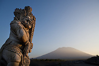 September 13th 2007- Bali, Indonesia- A statue stands guard at the end of a small bridge, as the Volcanic Mount Agung towers above the resort town of Candidasa in North Western Bali. Mount Agung last erupted in 1967.  Photograph by Daniel J. Groshong/Tayo Photo Group