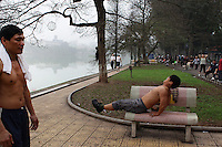 A man uses a park bench to exercise beside Hoan Kiem Lake, Hanoi, Vietnam.. For a county not know for it's sporting prowess, Hanoi, Vietnam's capital, appears to be gripped in a fitness frenzy. Before 6am street corners, parks and lake sides are a hive of activity as keep fit classes, Tai chi and personal exercise regimes are seen in abundance around the city. Particularly noticeable are Women's keep fit classes, often accompanied by loud poor quality western disco beat music as the occupants of the city get fit come rain or shine. Hanoi, Vietnam. 18th March 2012. Photo Tim Clayton