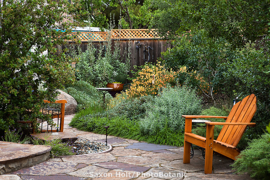 Stone path leading from patio with chair to perennial border in small space backyard drought tolerant California native plant garden