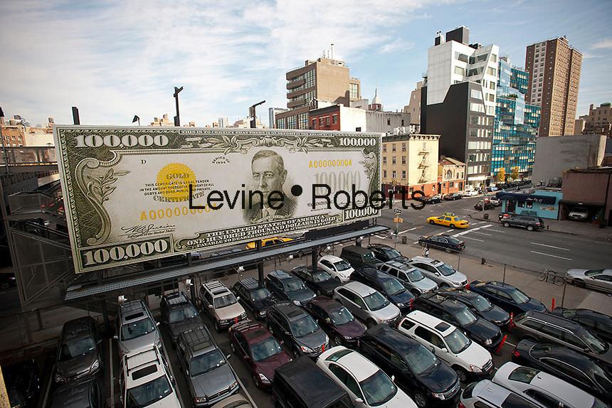"A billboard along the High Line Park in Chelsea in New York displaying ""The First $100,000 I Ever Made"" by the artist John Baldessari is seen on Friday, December 2, 2011. The artwork consists of an enlarged $100,000 bill which features the likeness of President Woodrow Wilson. The bills, of which only 42,000 were ever produced, were never circulated in public but were used for inter-bank transfers of funds up until 1935. The artwork is meant as a comment on the value of art and the economic crisis that the world is in. (© Richard B. Levine)"