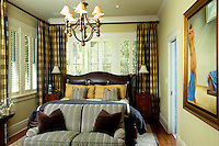 Clubby master bedroom with rich striped settee at the foot of the bed