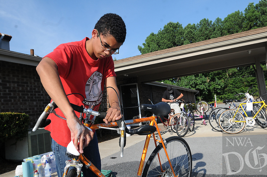 NWA Democrat-Gazette/FLIP PUTTHOFF<br /> Gabe Scott washes repaired bicycles Saturday August 8 2015 at First Christian Church in Bentonville.