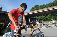 NWA Democrat-Gazette/FLIP PUTTHOFF<br /> Gabe Scott washes repaired bicycles Saturday August 8 2015 at First Christian Church in Bentonville.