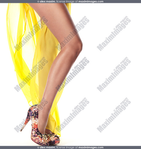 Sexy long legs of a young woman wearing yellow summer beach dress and high heel shoes isolated on white background