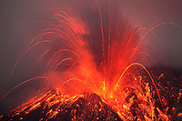 Sakurajima Volcano erupting at night with flowing lava, Japan.