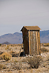 Tall weathered wooden outhouse with prop and wire to hold it down in the wind, Nevada