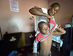 Eric Lovemore, 8, gets dressed in his home in Bulawayo, Zimbabwe, with help from his stepmother, Zandile Tohori. Lovemore suffered cerebral palsy and uses a wheelchair provided by the Jairos Jiri Association with support from CBM-US.