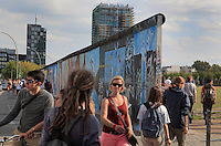 Section of the Berlin Wall including Flucht wie Tornado by Kasra Alavi, part of the East Side Gallery, a 1.3km long section of the Wall on Muhlenstrasse painted in 1990 on its Eastern side by 105 artists from around the world, Berlin, Germany. Many of the artworks are now damaged by graffiti. In the background is a new high-rise building under construction. Picture by Manuel Cohen
