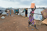 A woman carries water on her head inside a United Nations base in Juba, South Sudan, where some 34,000 people have sought protection since violence broke out in December 2013. More than 112,000 people currently live on UN bases in the war-torn country, most of them afraid of tribally targeted violence.