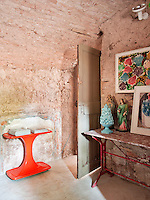 The walls of the bathroom have been left in their raw state with exposed brickwork. It is furnished with two console tables, one of which displays artwork and religious statues