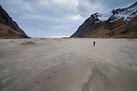 Female backpacker walks across the vast sands of Horseid beach, Moskenesøy, Lofoten Islands, Norway
