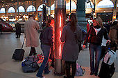 Paris, France.November 15, 2007..International trains at Gare Du Nord are rare on a nationwide day of strikes. Travelers stand near large heaters and check the  board frequently for trains that may or may not be departing. Many tracks remain empty as only 150 of the usual 700 TGV high-speed trains were running. French unions launch an open-ended strike in public transport (SNCF, RATP, ...), power utilities, education, and hospitals, in a major test for President Nicolas Sarkozy's reform plans. They are protesting against the scrapping of pension privileges that allow some public employees to retire as early as age 50...