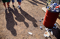 People walk past an overflowing garbage can at the Testicle Festival at the Rock Creek Lodge in Clinton, MT.  The Rock Creek Lodge in Clinton, MT, has hosted the annual Testicle Festival since the early 1980s.  The four day festival and party revolves around the consumption of so-called Rocky Mountain Oysters, which are deep-fried bull testicles.