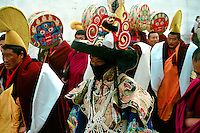 """A costumed dancer surrrouned by high rank monks and Mahakala drums players  is walking in the streets of the monastery of Labrang to join the Cham (tib:dance of the spirits), here: the so-caled """"Black hat dance"""". Xiahe, Gansu (Amdo),China."""