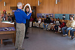 Oakland CA Docent and senior volunteer at Chabot Space and Science Center illustrating size of telescope lens to visiting 2nd graders and parent chaperones on school field trip