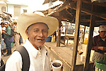 A farmer in straw hat with his morning coffee in Ixcan, Guatemala - a dusty, rough border town near Mexico