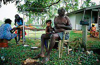 An Aboriginal family sits while some prepare for a Cleansing ceremony on Tiwi Islands.  <br /> Culture here seems to be more intact because the island  is removed from modern western culture.  <br /> Tiwi has two islands--Bathurst and Melville.  This ceremony is in the town of Garden Point on Melville Island, the 2nd largest island in Australia.