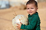 A boy hangs on to a damaged ball in the Zaatari Refugee Camp, located near Mafraq, Jordan. Opened in July, 2012, the camp holds upwards of 50,000 refugees from the civil war inside Syria. International Orthodox Christian Charities and other members of the ACT Alliance are active in the camp providing essential items and services.