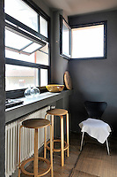 A detail of a grey room with an open square window in one wall. Two wooden high stools are placed below a window sill.