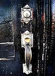 A silver door knocker on a black door