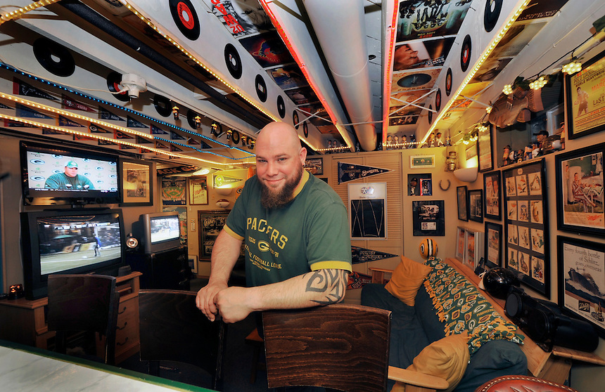 Client: Milwuakee Journal Sentinel<br /> Corey Mielcarz poses in his basement man cave at his Oklahoma Ave. home in Bay View on Wednesday, Oct. 26, 2011. Virtually every surface is covered with music and sports memorabilia, televisions and a wet bar.