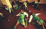Husa Muslim football team during Islamic prayers and exercices before football game..The implementation of Islamic Sharia Law across the twelve northern states of Nigeria, centres upon Kano, the largest Muslim Husa city, under the feudal, political and economic rule of the Emir of Kano. Islamic Sharia Law is enforced by official state apparatus including military and police, Islamic schools and education, plus various volunteer Militia groups supported financially and politically by the Emir and other business and political bodies. Fanatical Islamic Sharia religious traditions  are enforced by the Hispah Sharia police. Deliquancy is controlled by the Vigilantes volunteer Militia. Activities such as Animist Pagan Voodoo ceremonies, playing music, drinking and gambling, normally outlawed under Sharia law exist as many parts of the rural and urban areas are controlled by local Mafia, ghetto gangs and rural hunters. The fight for control is never ending between the Emir, government forces, the Mafia and independent militias and gangs. This is fueled by rising petrol costs, and that 70% of the population live below the poverty line. Kano, Kano State, Northern Nigeria, Africa