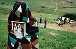 An unidentified woman holds her wedding photo as she mourns her husband who died of Aids a day before on November 28, 1999 in Izingolweni, Southern Natal, South Africa. The husband is being buried on the family plot and relatives and neighbors dig the grave, as the funeral is planned for the following day. Custom demands her to cover herself until the funeral is held. South Africa has one of the highest rates of HIV/Aids in the world and about 5.6 million people were infected in 2003. (Photo by: Per-Anders Pettersson)