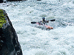 A man rides a kayak down the Gallatin River in Montana. People kayak on the Gallatin Rvier, between Big Sky and Bozeman, Montana.