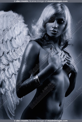 Beautiful naked blond woman with angel wings in dramatic  light artistic black and white photo